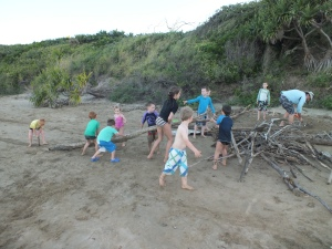 Kids working together to build a camp fire on the beach