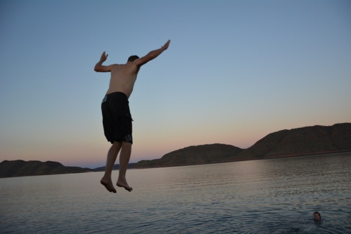 Matt jumping off the roof of the boat for a swim in the lake